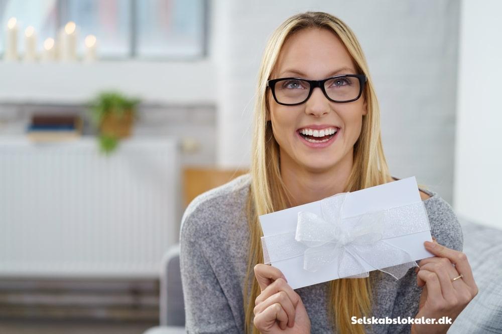 Pige holder en konvolut med en regel i